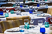 Restaurant tables set with glasses and plates in the harbour of Port d'Andratx, Mallorca, Balearic Islands, Spain