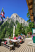 Several persons sitting on terrace of hut Rifugio Treviso Val Canali, Val Canali, Pala Group, Dolomites, UNESCO World Heritage Site Dolomites, Trentino, Italy