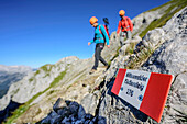 Signpost fixed-rope route Mittenwalder Klettersteig, two persons out of focus in background, fixed-rope route Mittenwalder Hoehenweg, Karwendel range, Upper Bavaria, Bavaria, Germany