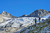 Two persons ascending to Reichenspitze, glacier Kuchelmoosferner and Wildgerlosspitze in background, Zillergrund, Reichenspitze group, Zillertal Alps, Tyrol, Austria