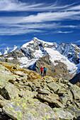 Two persons hiking, Dreiherrenspitze in background, Natural Park Zillertal Alps, Dreilaendertour, Zillertal Alps, South Tyrol, Italy