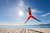 Young woman in red sports-dress jumps with red ball on wooden pier, Chiemsee, Bavaria, Germany