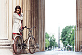 Young woman with her bicycle at dusk underneath the propylae, Königs Plaza, overlooking the Obelisk, Munich, Bavaria, Germany