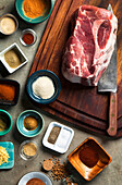 Cutting board with pork shoulder and variety of spices