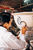 Artist painting pots in studio