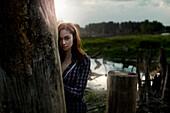 Pensive Caucasian girl leaning on wooden pillar