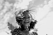 Smiling Caucasian girl with hair blowing in wind