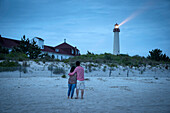 Asian couple watching lighthouse at beach