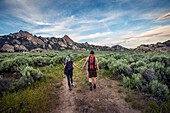 Caucasian couple hiking toward mountain