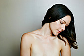 Pensive naked Caucasian woman near wall