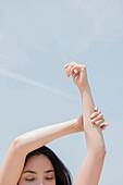 Hispanic woman stretching arms under blue sky