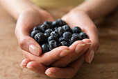 Hands of Hispanic woman holding blueberries