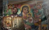 Black man holding worn religious book near mural