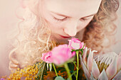 Caucasian teenage girl smelling bouquet of flowers