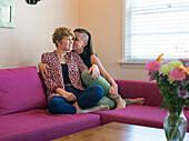 Caucasian lesbian couple kissing on sofa