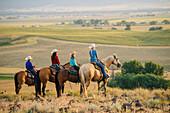 Cowboy and cowgirls on horseback admiring rural landscape