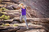 Caucasian woman running on rock formation