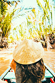 Caucasian woman floating in boat on rural river