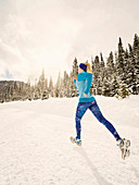 Caucasian woman running in snowy landscape