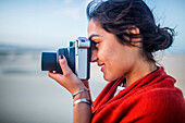 Mixed race woman photographing in desert