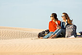 Mixed race women sitting in sand dunes