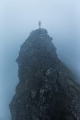 Person standing on the top of a rock on a foggy day, Faeroe Islands