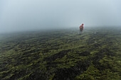 Person walking over a fog covered field, Faeroe Islands