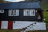Young boy running into his house, Faeroe Islands