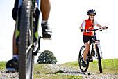 kids riding their bikes next to a meadow, Fuessen, Bavaria, Germany