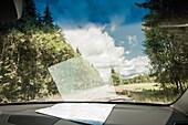 Blick durch die Frontscheibe des Autos mit der Landkarte auf dem Armaturenbrett, Landstrasse, Halland, Schweden