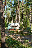 View to a camper in the woods of the campsite of castle Lacko, lake Vanern, Kallandso, Lidkoping, Vastergotland, Sweden