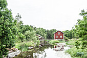 Alte Mühle mit rotem Holzhaus auf dem Land in Västergötland, Schweden