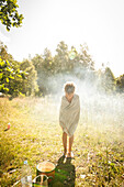 child after a shower in a meadow with morning sun, Halland, Sweden
