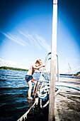 Junge klettert vom Bootssteg in das Wasser, Öregrund, Uppsala, Schweden