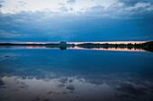 Untergehende Sonne auf einem See in Smaland, Schweden