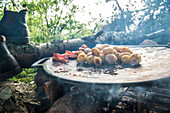 Close up of a frying pan on a campfire with roasted bacon and potatoes, Lake Vanern, Vastergotland, Sweden