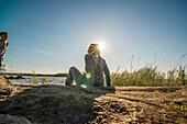 Frau sitzt auf einem Felsen am Vänernsee in der Sonne und lacht mit ihrem Kind, Smaland, Schweden