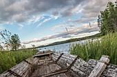 Verrottetes Fischerboot am Ufer eines kleinen Sees im Abendlicht, in der Nähe von Munkfors, Värmland, Schweden