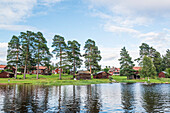 view from water to the village of Bodarna with its red wooden houses, Solleron, Dalarna, Sweden