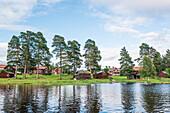 Sicht vom Wasser auf das Dorf Bodarna mit seinen roten Holzhäuser, Sollerön, Dalarna, Schweden