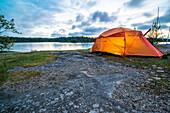 Auf den Klippen direkt am Wasser steht das orange leuchtende Zelt im Abendlicht, Anskarsklubb, Öregrund, Uppsala, Schweden
