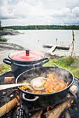 In einer Pfanne werden frisch gesammelte Pfifferlinge auf dem Lagerfeuer gebraten, im Hintergrund Bootssteg und Bucht, Anskarsklubb, Öregrund, Uppsala, Schweden