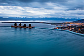 Four people relax in infinity pool at Arakur Ushuaia Resort and Spa and overlook the Beagle Channel and city at dusk Ushuaia, Tierra del Fuego, Patagonia, Argentina