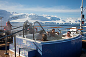 Passengers relax in a hot tub aboard expedition cruise ship MV Sea Spirit (Poseidon Expeditions) with view of snow-covered mountains Gerlache Strait, Graham Land, Antarctic Peninsula, Antarctica