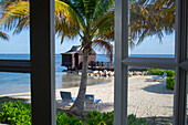Palm trees and overwater spa cabana of Half Moon Resort seen through window of Royal Suite in Royal Court accomodation Rose Hall, near Montego Bay, Saint James, Jamaica