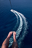 Aerial of photographer's feet and boat wake in Caribbean Sea during parasail activity at Half Moon Resort Rose Hall, near Montego Bay, Saint James, Jamaica