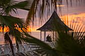 Couple admire sunset from pavillion on jetty at Half Moon Resort Rose Hall, near Montego Bay, Saint James, Jamaica