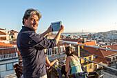 Tourist mit Tablet, Aussicht von Dachterrasse, Park, Bar auf Parkhaus, Dach, über der Stadt, junge Leute nach Feierabend, Touristen, relaxed, entspannt, chillen bei einem Drink, Santa Catarina Kirche, Blick über Lissabon, Portugal