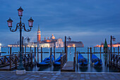 View from St. Mark's Square with gondolas and lanterns to the island of San Giorgio Maggiore with its namesake church in the blue of the night, San Marco, Venice, Veneto, Italy
