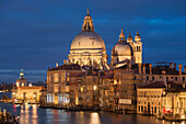 Overlooking the Grand Canal with gondolas and illuminated houses and the church of Santa Maria della Salute in the blue of the night, Dorsoduro, Venice, Veneto, Italy